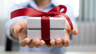 A man holds a gift box tied with a red bow toward the camera.